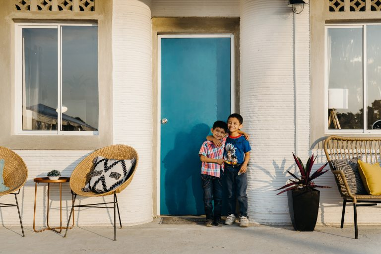 Two young brothers in front of their 3d-printed home