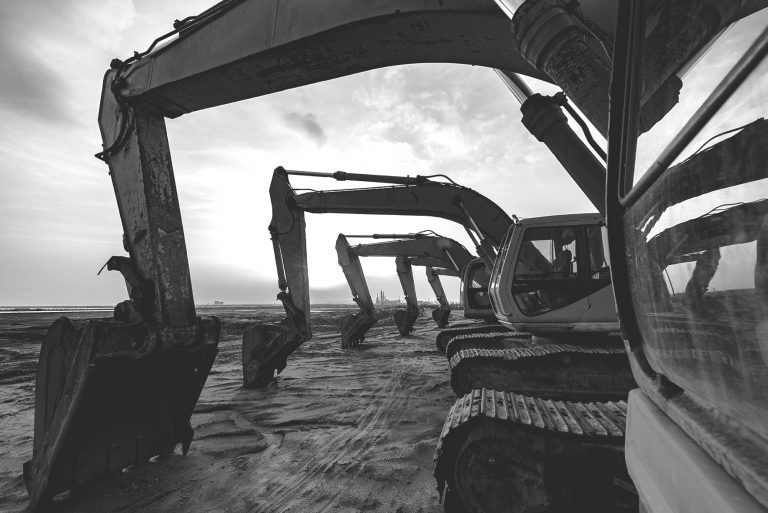 multiple excavators parked in a row