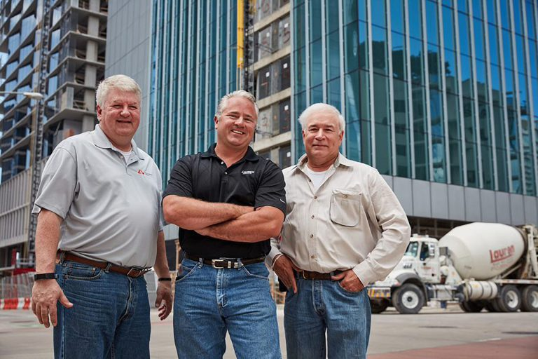 3 men standing in front of building and concrete mixer truck