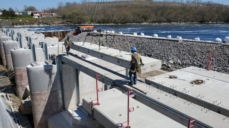 construction workers laying concrete dam