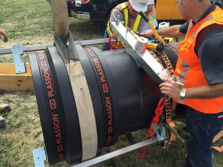 construction worker measuring Plasson polythylene pipe